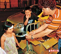 Mr. Chow (周福祥) handing out hamburgers to kids.
