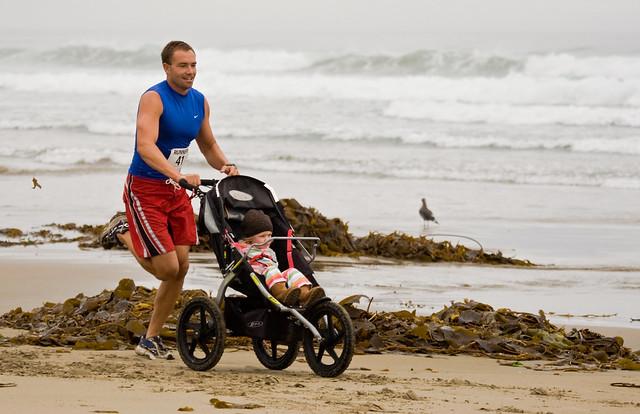 Man running while pushing a baby trike - Runners at 1st Annual Rock 2 Rock 5 Mile Fun Run