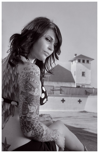 A great photo of this tattooed lady with feathered wings on her back and