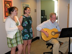 Two students from Wiscasset sing and a teacher plays a guitar during a musical performance at the Maine Department of Education.