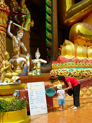 Putting coins on the conveyor belt at Wat Tham Seua