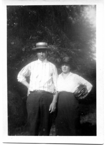 Man and woman standing in front of a bush.