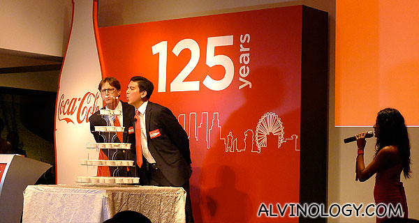 Two Coca-Cola top management staff blowing a birthday cake