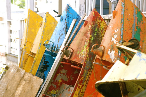 a series of brightly painted but rusting dinghies leaning against a wall.