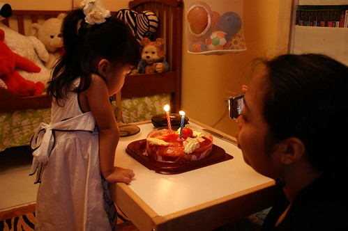 Mama coaxing me to blow out the candles because she wants to eat the cake.