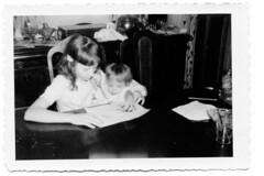 Ginny helps Dona draw at Grandma's diningroom table.