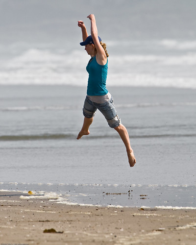 3 of 8 Girl dances (jumps) at water's edge on Morro Strand State Beach
