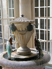 Fountain of spa water in the Pump Room, looking over the Roman Baths, Bath, UK