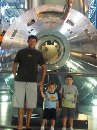 J and the boys in front of an Apollo space capsule.