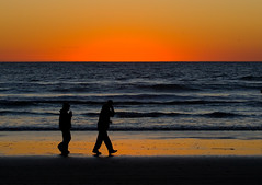 Couple walk in silhouette on Morro Strand Stat...