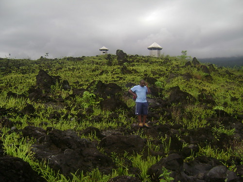 Mathew stands on lava from Mount Cameroons 2001 eruption.