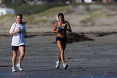 Two young girls jog along Morro Strand State Beach