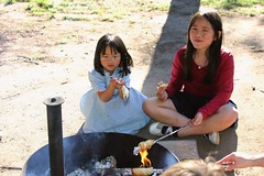 The Girls Making Cinnamon Rolls Over the Campfire