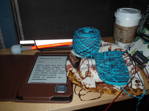 Kaylee sock, my cybook and my white cane sitting on the table at Starbucks