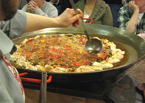 adding broth to paella