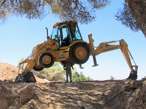 Driver examining the underside of the bulldozer