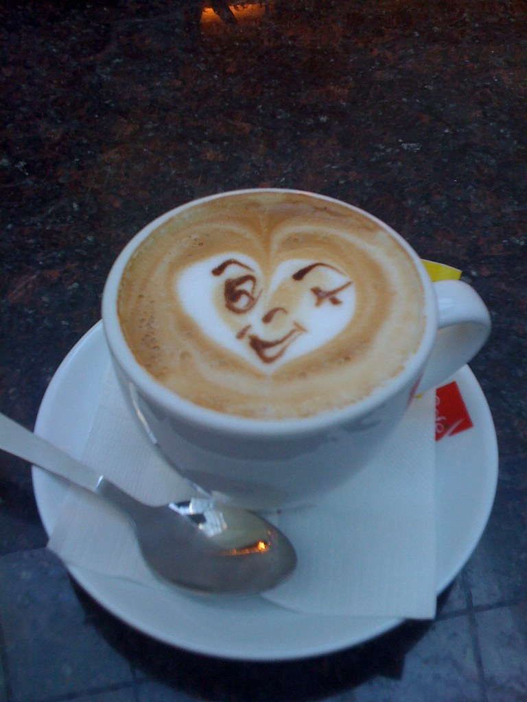 Coffee with a funny face enclosed in a heart drawn on the foam