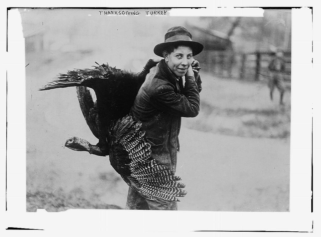 A man carries a turkey slung over his shoulder