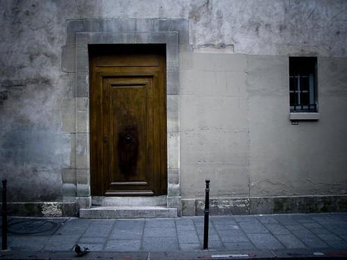 회색빛 집에 갈색 문이 있다.