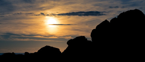 Setting sun over silhouetted rocks