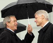 GW Bush and Bill Clinton share an umbrella