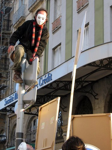 A guy in a white mask climbs on a sign at the strike in Valence.
