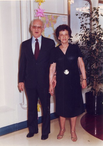 A middle-aged white couple, the man balding and wearing glasses and a suit and tie, the woman in a semi-formal black dress