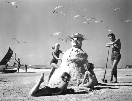 "Three girls making a ""sandman"" at the beach"