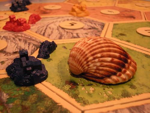 Catan: Monstre Sauren en uns prats de pastura d'un poblat