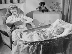Woman reads as baby sleeps