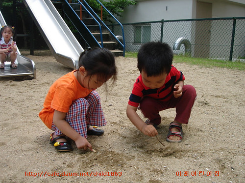 image of a boy and a girl scribbling on the sand