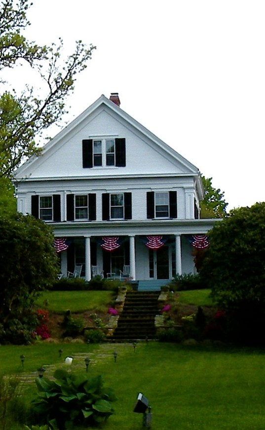 A white Greek Revival house with deep porch and patriotic bunting on Cape Cod.