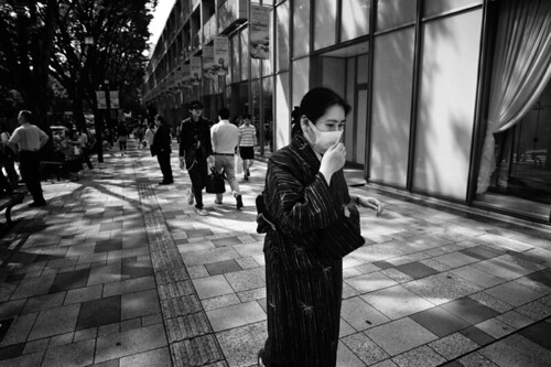 A woman in a mask strolls down Omotesando in Tokyo, May 2009, a week after the first case of the A/H1N1 flu was detected in Tokyo.