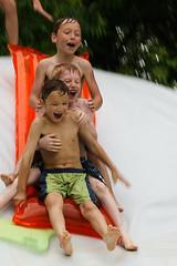 Three happy kids slide down a slip-n-slide