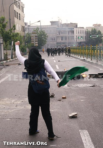 single protestor shakes fist at riot police in Tehran