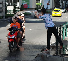 67 - People on the street douse a passing motorcycle to celebrate Songkran