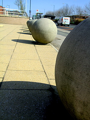 concrete balls decorating the entrance to a footpath (and blocking entrance for cars) on a new housing development off the main road. I like the architectural lines of the photo though, between the pavement slabs, the road, the balls, and the railing of the bed in the background.