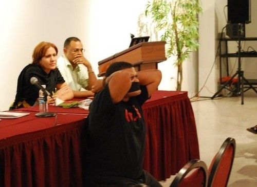 realizando la primera parte del performance, mientras Maribel Ortiz y Miguel Angel Fornerin observan