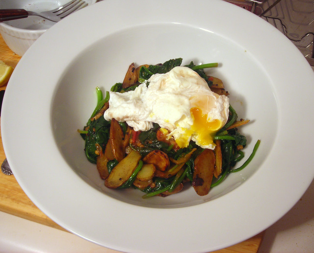 Poached farm egg over pan-fried potatoes, tomatoes and spinach with Indian spices