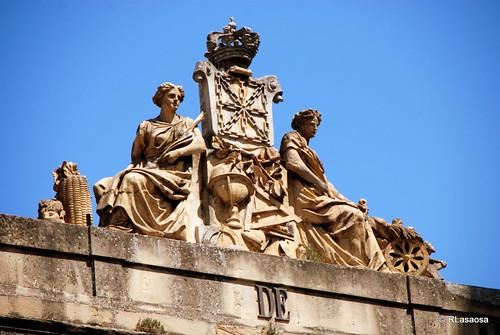 Grupo escultórico situado en lo alto del edificio del INAP (Instituto Navarro de Administración Pública), antigua Escuela de Comercio, situado frente a la Catedral.