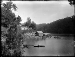 River scene with rowing boat and boat shed