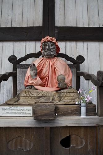 En ekstra heldig statue utenfor tempelet som hadde fått seg en regnfrakk.