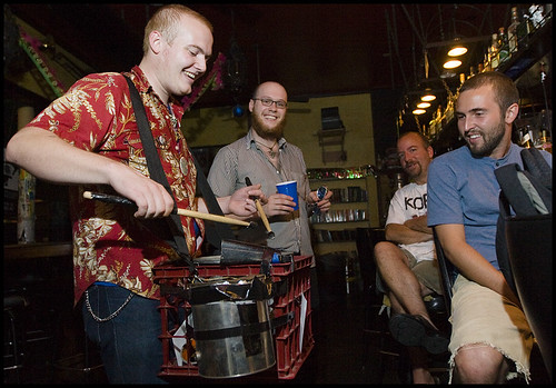 Hooten Hallers band member Andy Rehm plays a beat to the background music at The Blue Fugue on Thursday as fellow band member John Randall, Rocheport resident Richard Petty and Columbia resident John Thomas listen.