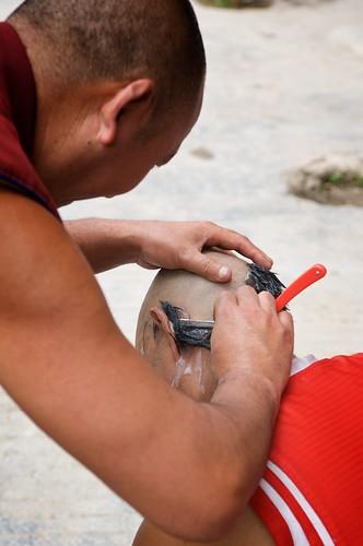 Tibetan Buddhist monks take turns shaving eachothers heads in Ganze, Tibet (China).
