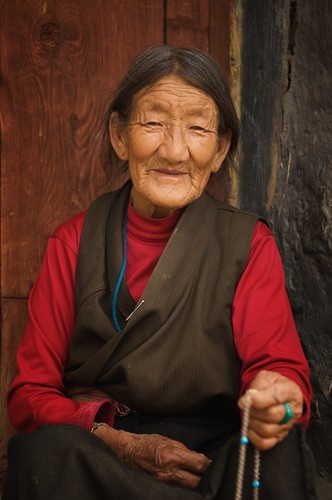 An elderly Tibetan woman sits on her doorstep in Ganze, Tibet (China).