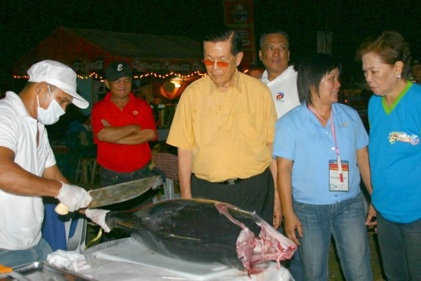 Senate President Johnny Enrile watch a tuna being sliced for sashimi at the Tuna Food Park inside the Oval Plaza. Enrile was the Opening Programs Keynote Speaker.