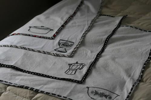 Four embellished tea towels