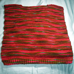 Photo of back of Christmas Spices Cardigan, knit in alternating stockinette stitch and garter stitch.  Stockinette stitch is knit in semi-solid burgundy wool (Galenas Merino in Cinnamon Spices colorway).  Garter stitch is knit in variegated red, burgundy, brown, light blue, and olive green wool (Galenas Merino in Gingerbread House colorway).  Cardigan is Lion Brand's Striped Cardi pattern in size 5T.