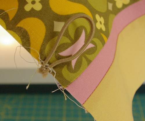 Sew on elastic about one eighth from fabric edge with about a quarter inch hanging of the edge by you.