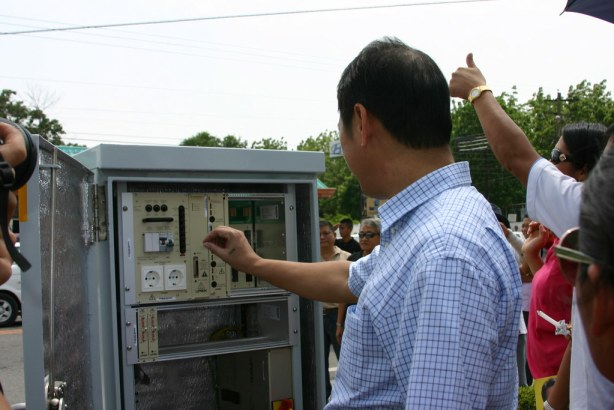 Mayor Jun Acharon fiddling with the different switches to start the Traffic Lights System at the National Highway.  - photo by Bariles
